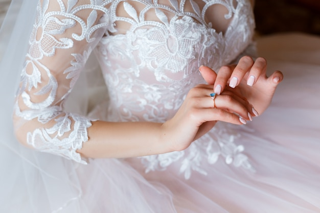 Ein goldener verlobungsring mit einem blauen edelstein auf der hand der braut. zartes, rosa hochzeitskleid mit spitzenkorsett