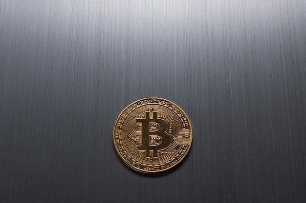 Ein goldenes bitcoin auf einem metallischen hintergrund