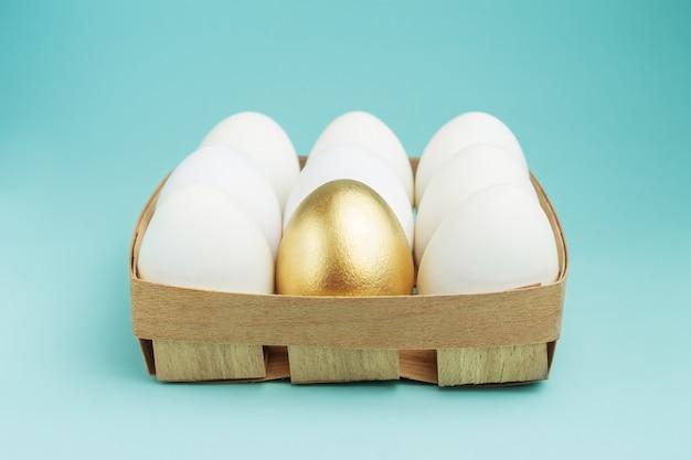Ein goldenes ei unter weißen eiern in einer holzkiste auf einer blauen tabelle. konzept der einzigartigkeit.