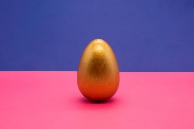 Ein goldostereier auf blauem und rosa hintergrund