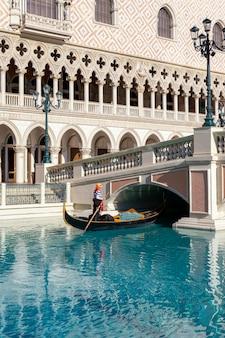Ein gondoliere am venetianischen hotel und am kasino mit einem ruder, das auf einen kanal auf einer gondel in las vegas, nevada, usa schwimmt.