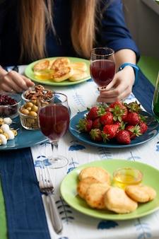 Ein gourmet-frühstück für zwei: syrnyky, erdbeeren, traubensaft und verschiedene vorspeisen.