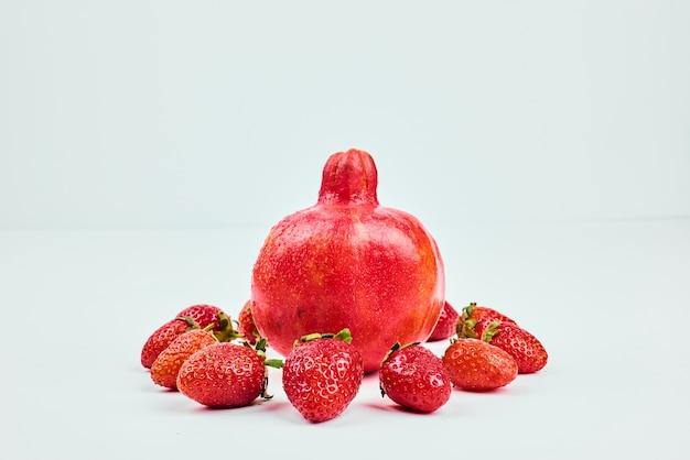 Ein granatapfel mit erdbeeren auf weiß isoliert.