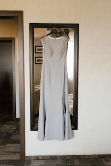 Ein grau-silbernes elegantes kleid hängt im raum am spiegel. kleid für eine erwachsene brautjungfer