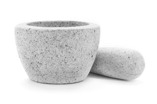 Ein grauer granitmörser und stößel isolieren auf einer weißen oberfläche.