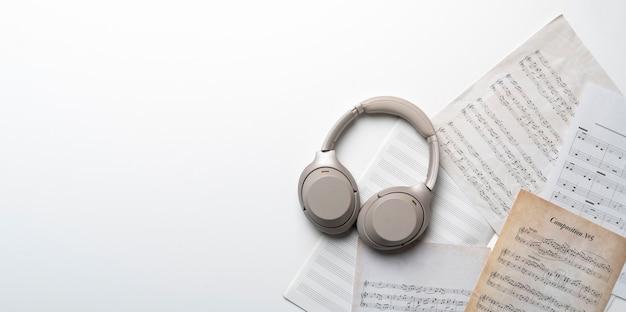 Ein grauer kopfhörer auf dem notenpapierblatt