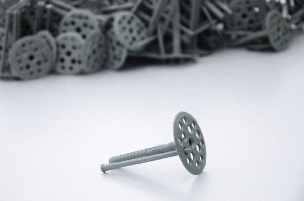 Ein grauer kunststoffdübel (befestigung) zur wärmedämmung mit runden schirmkappen liegt auf einer grauen schaumpolystyrolplatte