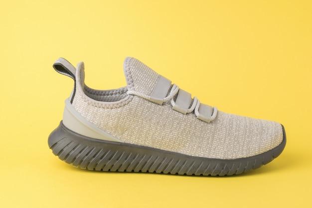 Ein grauer sneaker mit hohen sohlen auf gelbem grund. sportlicher lebensstil. farben 2021.