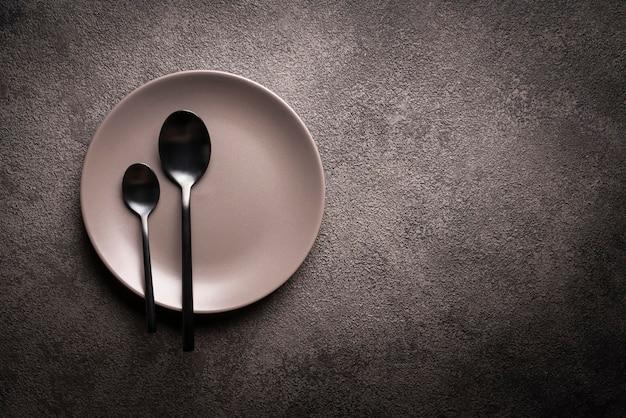 Ein grauer teller und löffel auf einem schwarzen tisch. copyspace-konzept für die werbung für gerichte oder restaurantmenüs, eine einladung zu einer dinnerparty oder feier.