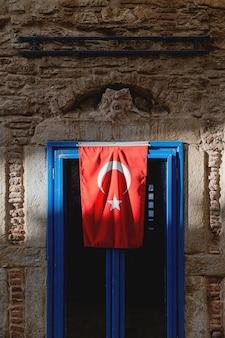 Ein graues gebäude mit türkischer flagge auf blauem fenster im sonnenlicht