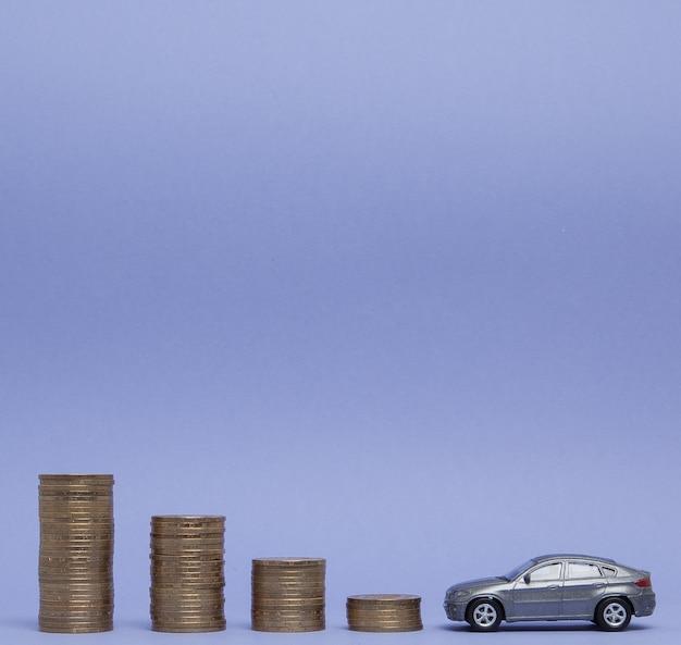 Ein graues modell eines autos mit münzen in form eines histogramms auf einem lila hintergrund. konzept der kreditvergabe, ersparnis, versicherung.