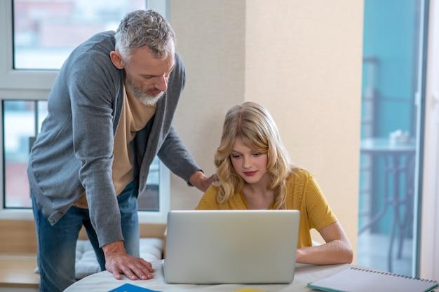 Ein grauhaariger mann, der neben seiner tochter steht, während sie am laptop arbeitet