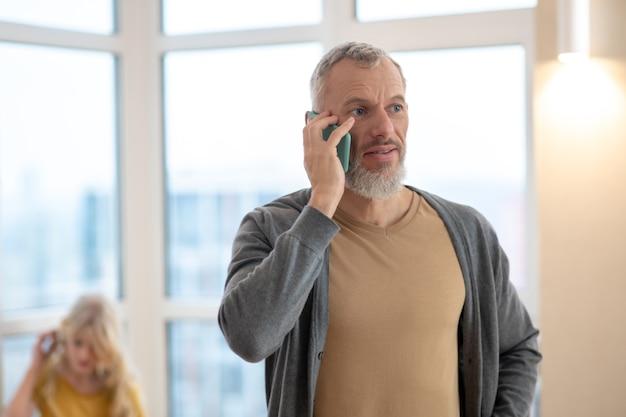 Ein grauhaariger reifer mann, der am telefon telefoniert und zufrieden aussieht