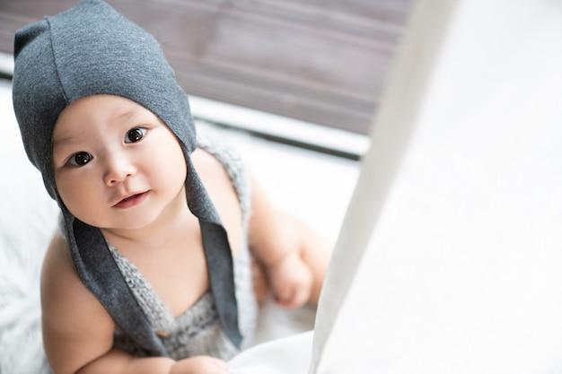 Ein grauhaariges baby, das auf dem boden sitzt, schaut auf, sein gesicht ragt zwischen dem vorhang hervor