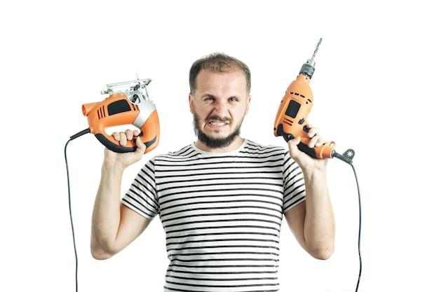 Ein grinsender mann in einem gestreiften t-shirt hält einen bohrer und eine elektrische stichsäge in den händen isoliert auf weiß