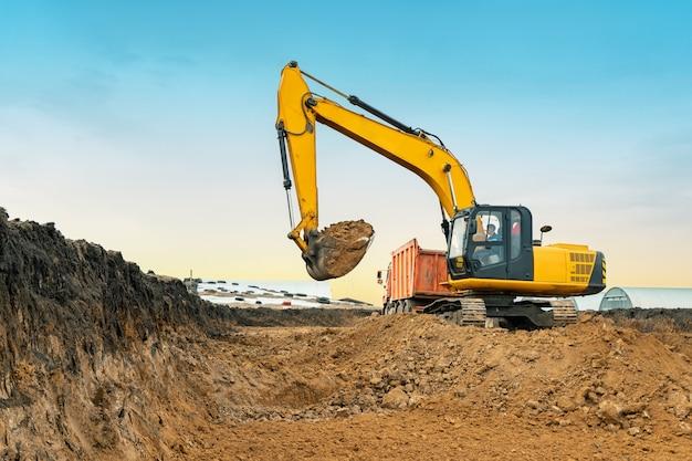 Ein großer baubagger von gelber farbe auf der baustelle in einem steinbruch zum abbau. industrielles image.