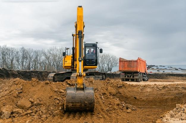Ein großer baubagger von gelber farbe auf der baustelle in einem steinbruch zum abbau. industrielles image