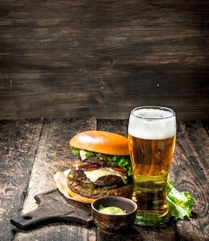 Ein großer burger mit rindfleisch und einem glas bier