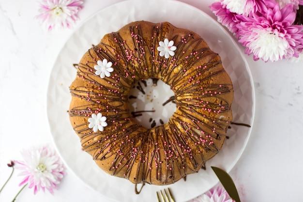 Ein großer cupcake verziert mit schokoladenganache und zuckergänseblümchen. von oben betrachten. cupcake mit orangen und kandierten früchten