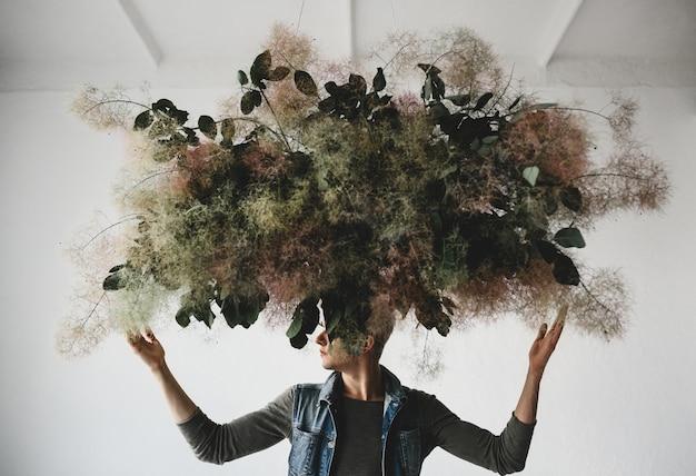 Ein großer dekorativer blumenstrauß aus grünen blättern und moos hängt über dem kopf des mannes