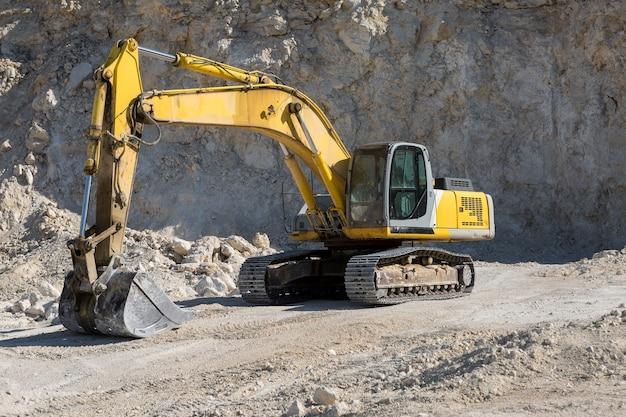 Ein großer gelber raupenbagger baut in einem steinbruch gestein ab.