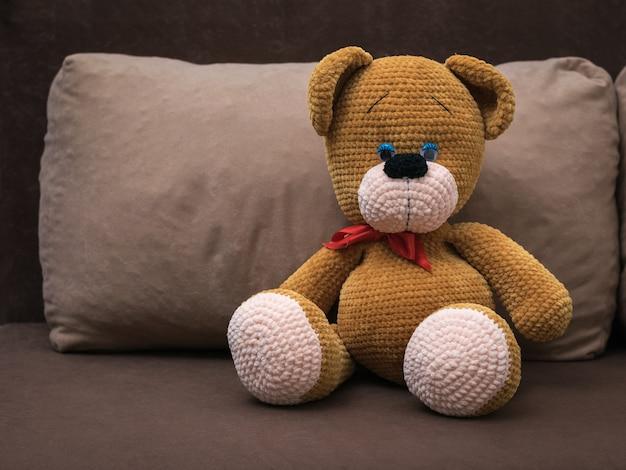 Ein großer gestrickter bär mit rotem stirnband auf einem weichen sofa. schönes strickspielzeug.