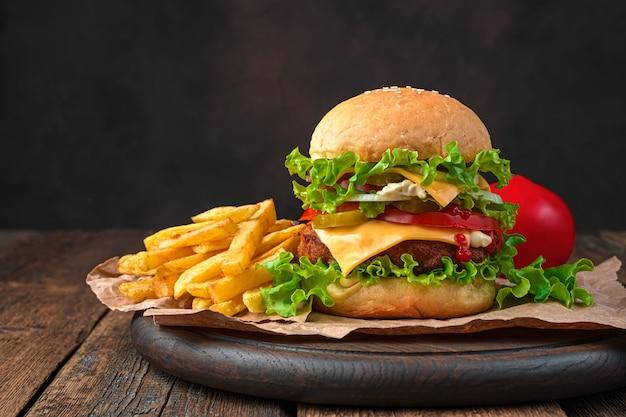 Ein großer hausgemachter burger und pommes frites an einer braunen wand. seitenansicht, kopienraum.