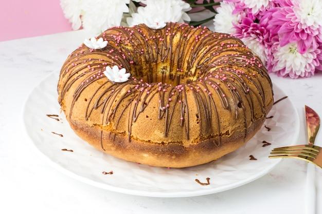 Ein großer kleiner kuchen gegen eine chrysantheme. ein kleiner kuchen mit orangen und kandierten früchten. schokoladen-ganache und weiße zucker-gänseblümchen