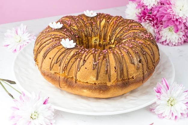 Ein großer kleiner kuchen gegen eine chrysantheme. ein kleiner kuchen mit orangen und kandierten früchten. schokoladen-ganache und weiße zuckergänse