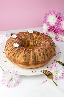 Ein großer kleiner kuchen gegen eine chrysantheme. ein kleiner kuchen mit orangen und kandierten früchten. schokoladenganache und weiße zuckergänse. vertikale ausrichtung