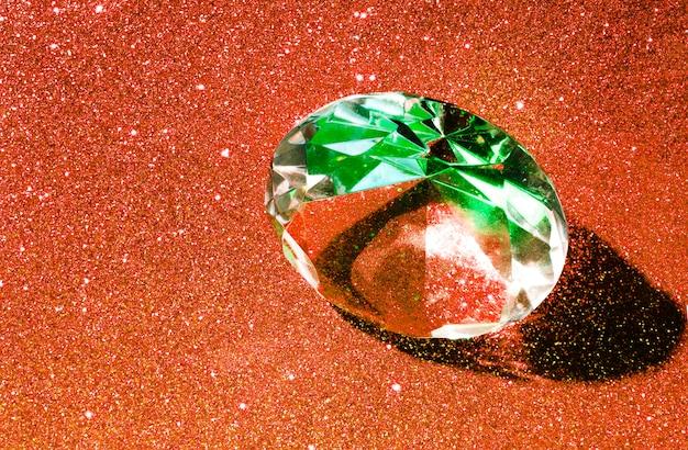 Ein großer kristalldiamant auf einem orange glänzenden hellen hintergrund