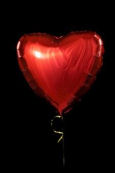 Ein großer roter herzballgegenstand für geburtstag, valentinstag. isoliert auf schwarzem hintergrund.