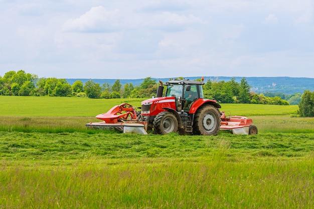 Ein großer roter traktor mit zwei mähern mäht das grüne gras auf einem silo.