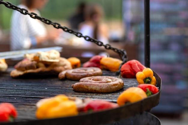 Ein großer runder grill auf den kohlen, in dem gegrilltes farbgemüse und frische fleischwürste gekocht werden. lebensmittel und ausrüstung zum kochen auf einem food festival