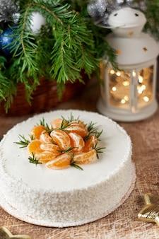 Ein großer runder kuchen, dekoriert mit mandarinenscheiben auf einem weihnachtstisch mit einer laterne und einem fichtenzweig. vertikaler rahmen
