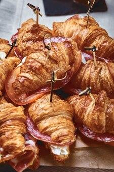 Ein großer satz vieler croissants mit verschiedenen füllungen auf einem tisch an einer grauen wand.