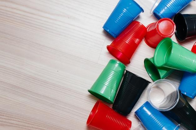 Ein großer stapel mehrfarbiger plastikbecher auf dem boden mit freiem platz. umweltverschmutzung durch menschlichen abfall