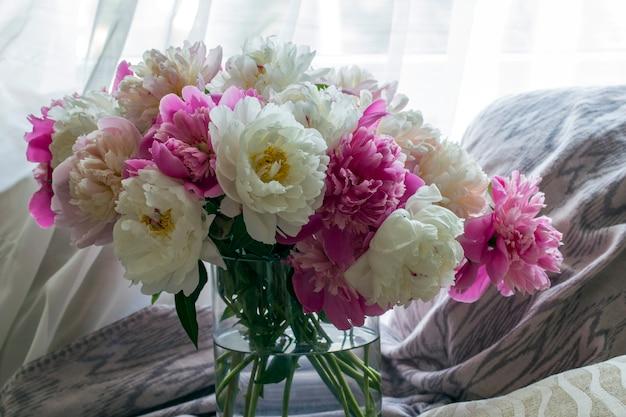 Ein großer strauß pfingstrosen in einer vase liegt auf dem tisch