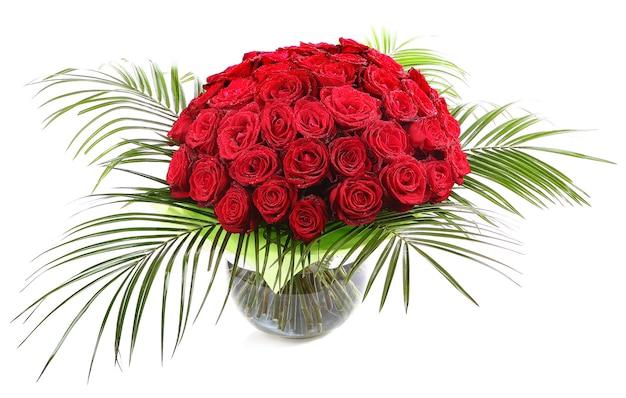 Ein großer strauß roter rosen in einer transparenten glasvase. das isolierte bild auf einem weißen hintergrund.
