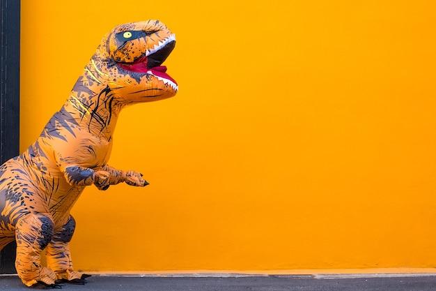 Ein großer und großer dinosaurier, der mit orangefarbenem hintergrund spaß hat und spaß hat - kopieren sie und leeren sie platz, um ihren text hier zu schreiben