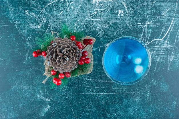 Ein großer weihnachtstannenzapfen mit einer glasschale blauen getränks.