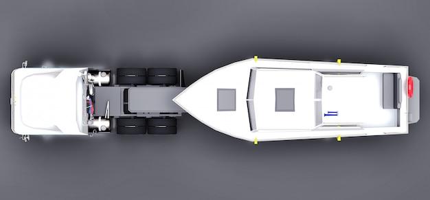 Ein großer weißer lkw mit einem anhänger für den transport eines bootes auf einer grauen oberfläche