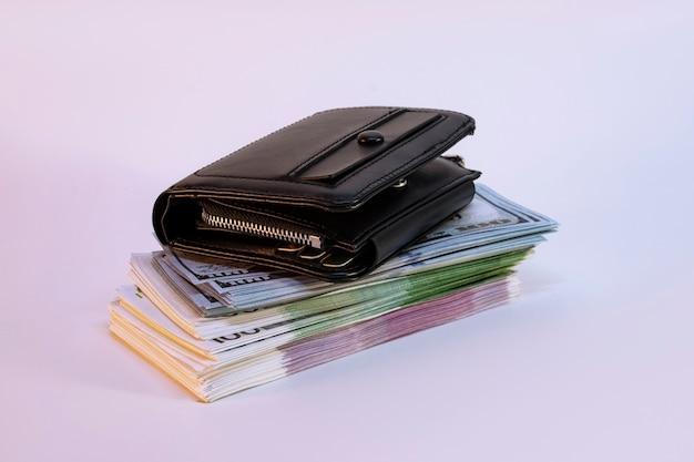 Ein großes bündel dollar und euro mit einer brieftasche auf hellem hintergrund.