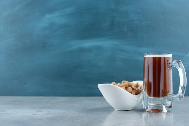 Ein großes glas bier mit weißem teller voller cashewnüsse. foto in hoher qualität