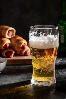 Ein großes glas helles bier und würstchen im teig auf dem brett