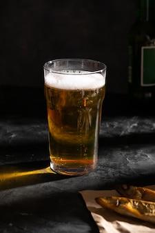 Ein großes glas helles bier und zwei getrocknete fische