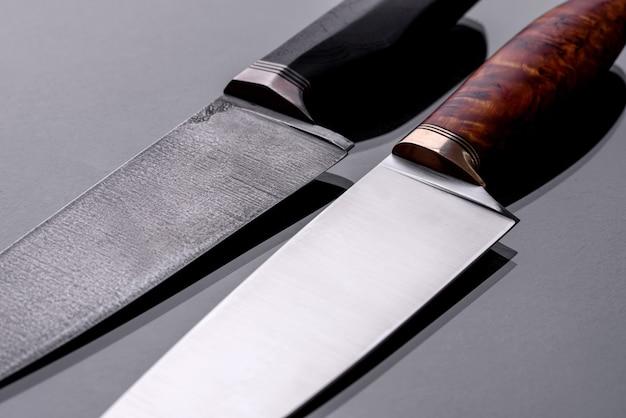 Ein großes handgemachtes jagdmesser, das auf einem dunklen monotonen hintergrund liegt