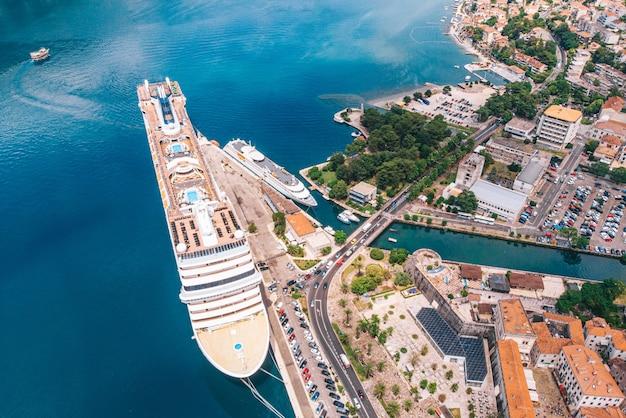 Ein großes kreuzfahrtschiff vor anker in der bucht von kotor, montenegro. luftbild an einem sonnigen tag.