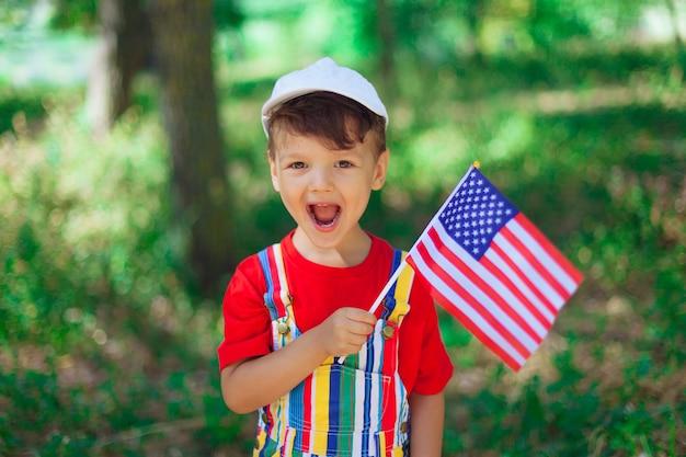 Ein großes porträt eines schönen kindes der junge lacht und lächelt in hellen kleidern ein rotes t-shirt auf dem ...