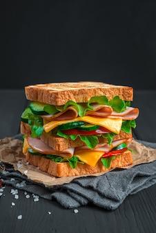 Ein großes sandwich mit geröstetem toast-schinken-käse-tomaten und gurke auf schwarzem hintergrund